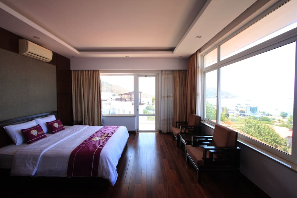 Bedroom with full sea view, double bed, wood floor, sofa, working desk and big toilet