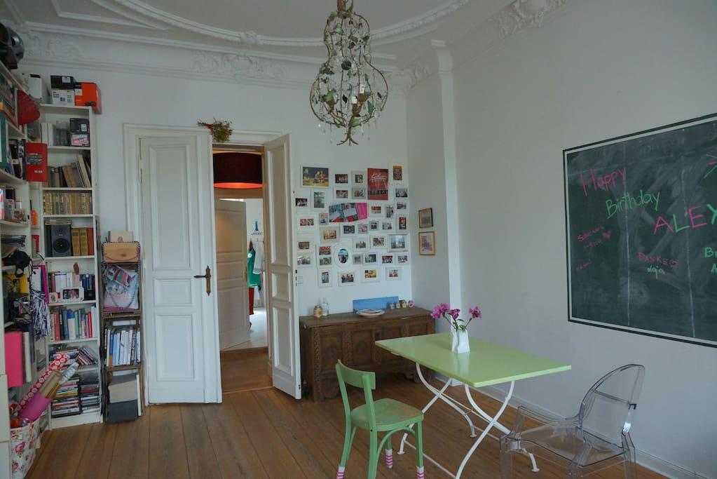 Esstisch und Bücherregal sind im vorderen Teil des Wohnzimmers