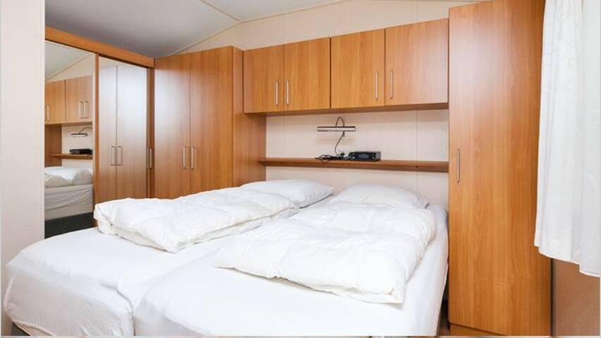 slaapkamer 2 met veel kastruimte en luxe boxspringbed, Camperen met hoofdletter C