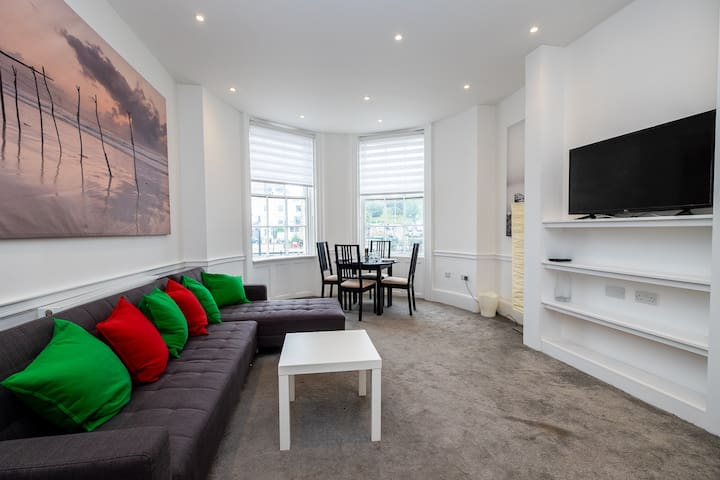 Bright and spacious living area with a huge L shaped sofa that splits into a single and a double sofa bed