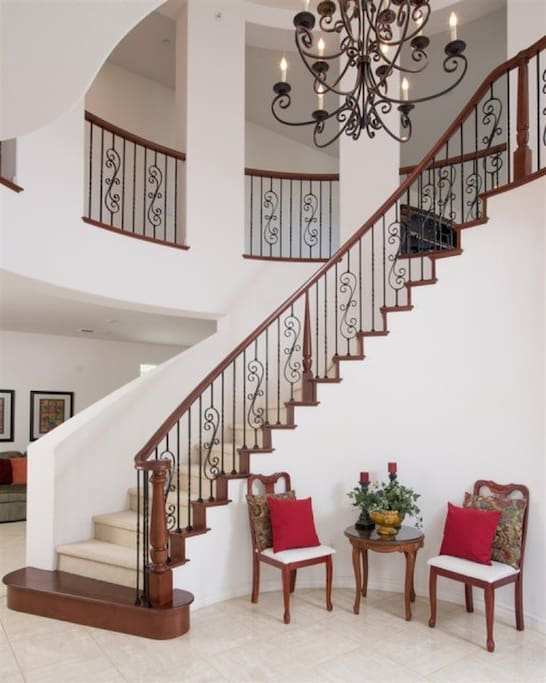 As you walk up the impressive winding staircase to the second floor, you oversee the living room and courtyards, and dining room.