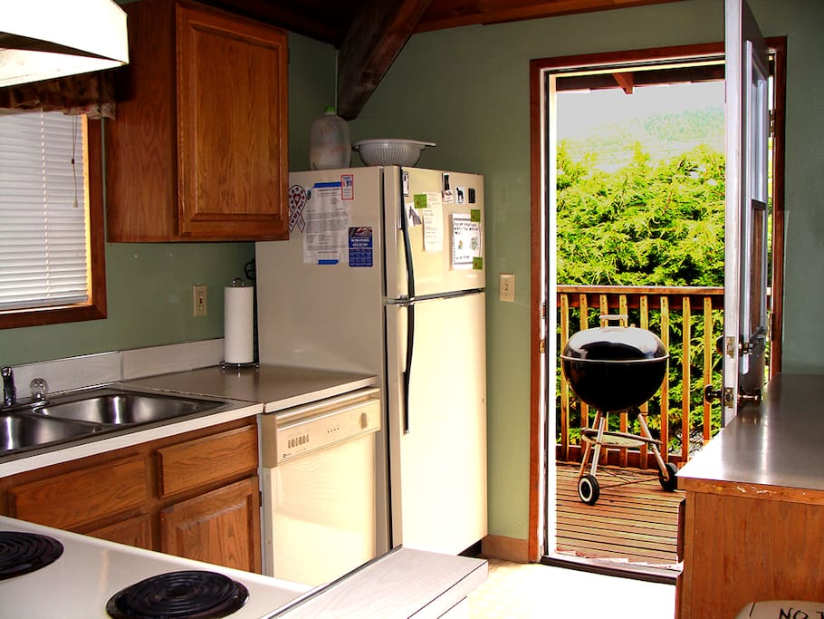 The kitchen may be small but is well stocked and has access to back deck w//BBQ