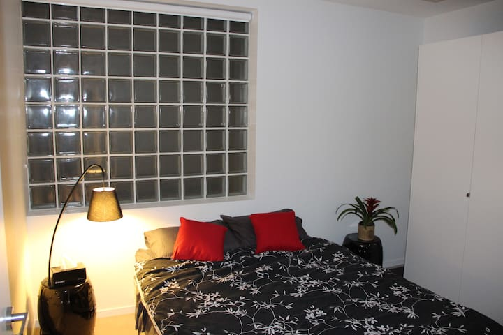 Queen size bed, built in wardrobes and large window.