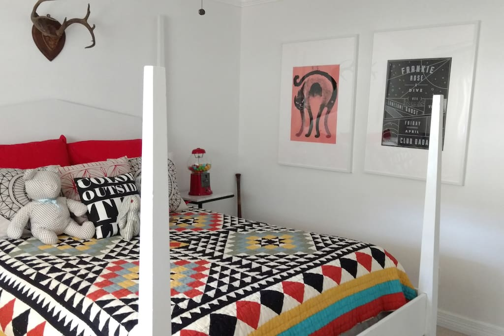 Sunny queen bedroom boasts vintage furniture and artwork.