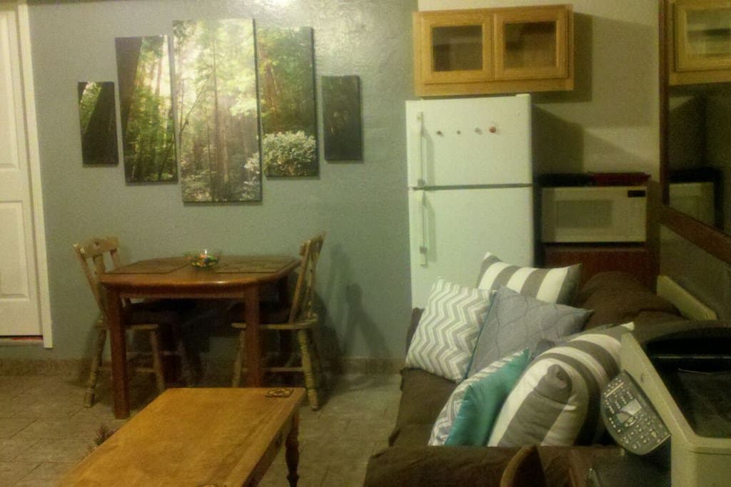 Dining room table, refrigerator and kitchen area