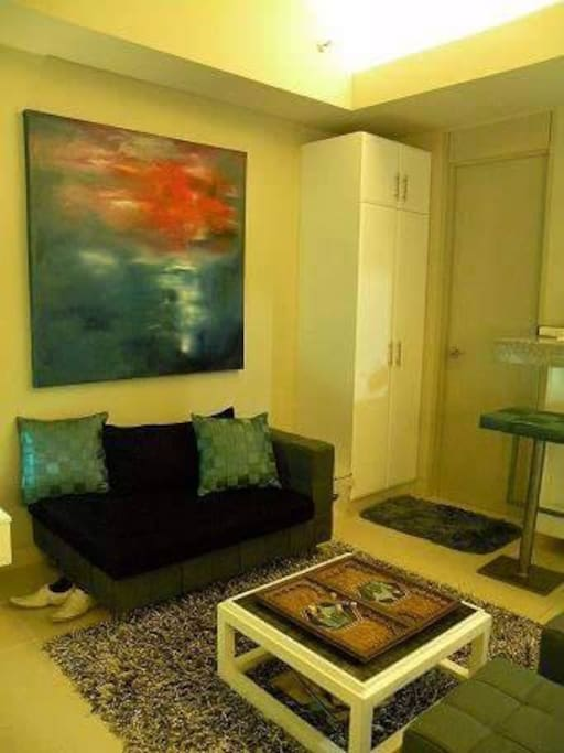 40sqm spacious studio with custom furniture-sofa, artwork, storage, coffee table and ottomans