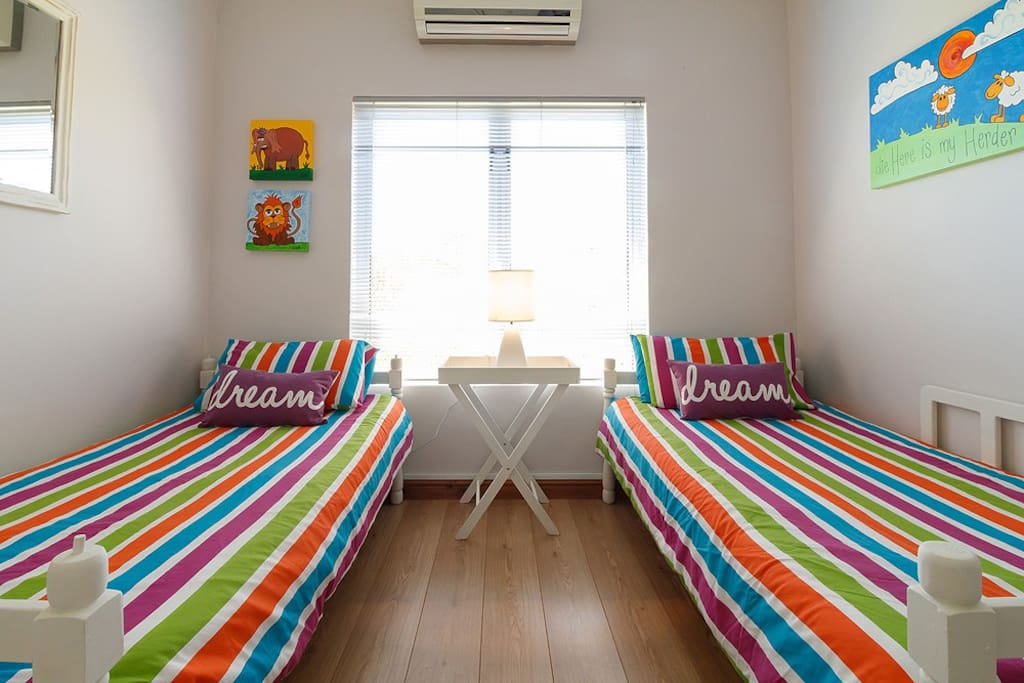 Bedroom 2 *2 x single beds with quality linen *Build in cupboards *Air conditioning (T&C)