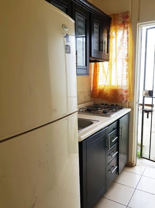Cocina con estufa, refrigerador, utensilios de cocina para cuatro personas