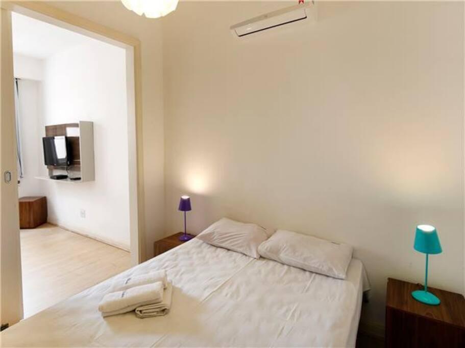 Ambiente com cama de casal e split e closet, e outro ambiente, com sofá-cama e ar condicionado de janela