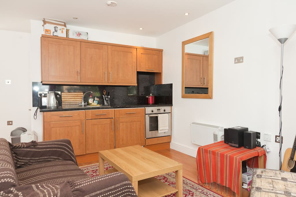 Bright open plan area with sofa and kitchenette