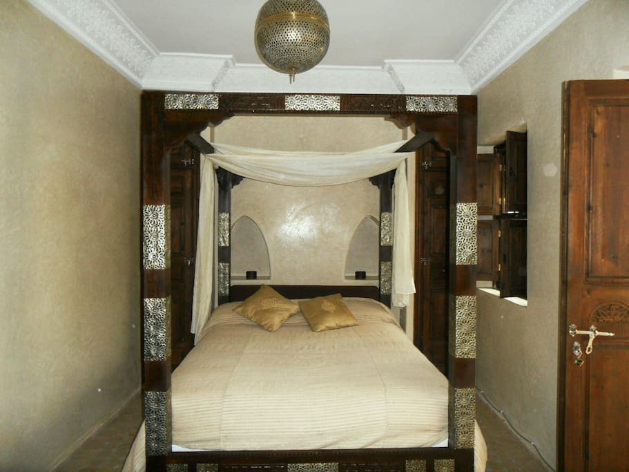 the cedar-wood four poster bed in room Turiya