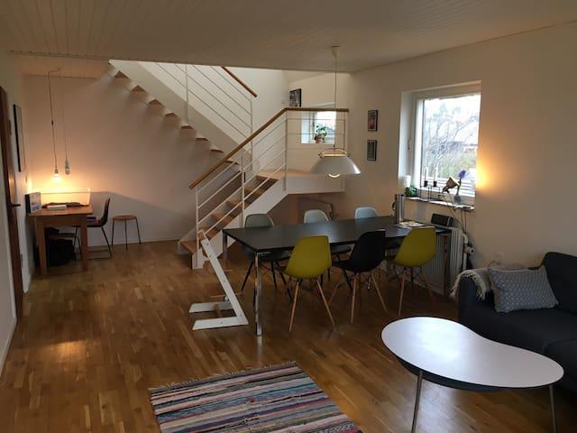 Stue med spiseplads og trappe til 1. sal