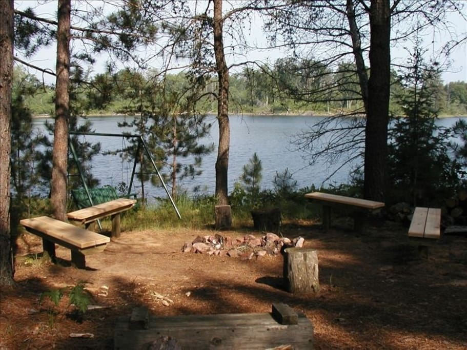 Enjoy a bonfire next to the lake while relaxing on a bench swing.