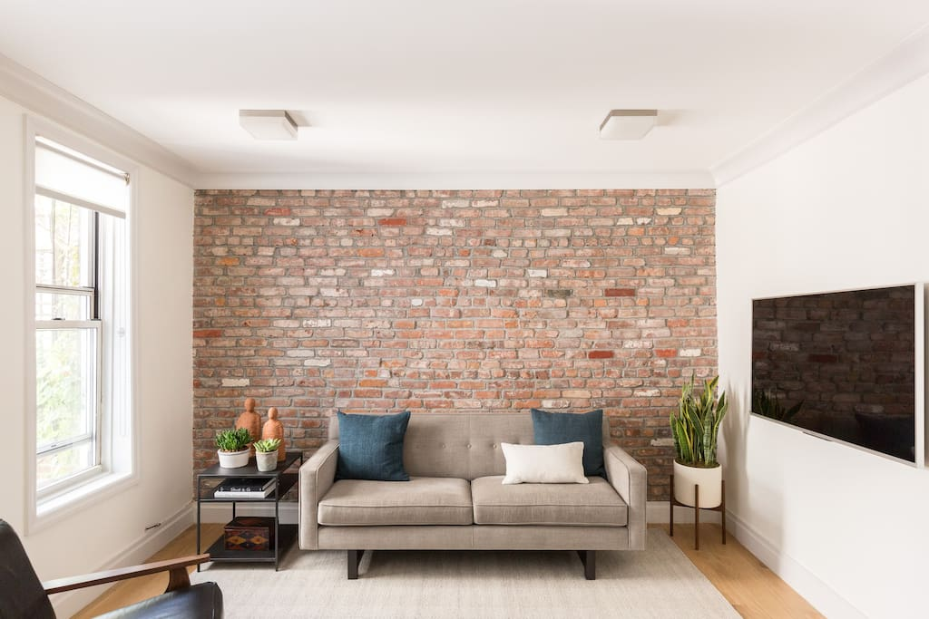 Original exposed brick from the 1920's, modern new couch and unique decoration touches via personal travel from around the world.