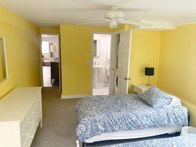 Yellow bedroom with Queen and twin Tempur-Pedic beds, looking toward en-suite bathroom and living room.