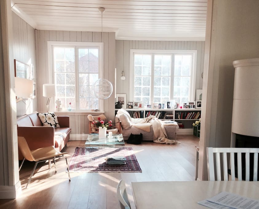 Spacious, big, classic livingroom, original windows, wonderful daylight. Eclectic style with design classics. Daybed by one of the windows, classic leather sofa. Glimpse of the fireplace in the kitchen.