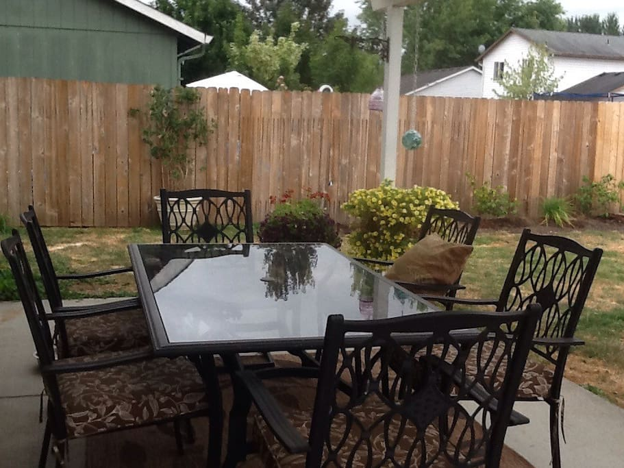 Covered patio with hummingbird and bird feeders for relaxing and enjoying nature.
