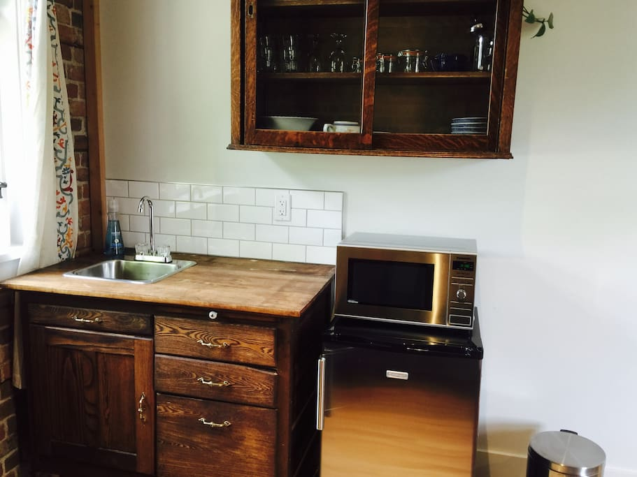 Kitchenette with antique cupboards, modern fixtures and appliances (microwave and fridge), dishes, etc. The little fridge even has a teeny freezer.