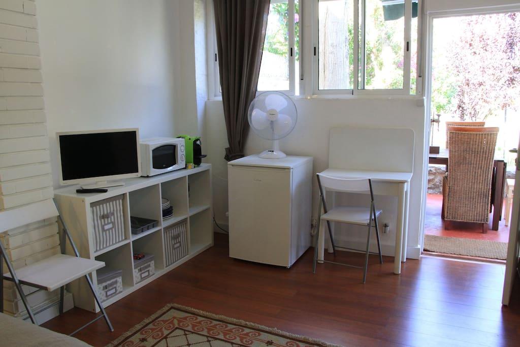 LCD, micro-ondas, ventiladores, máquina de café, mini frigorífico, copos, talheres, pratos.