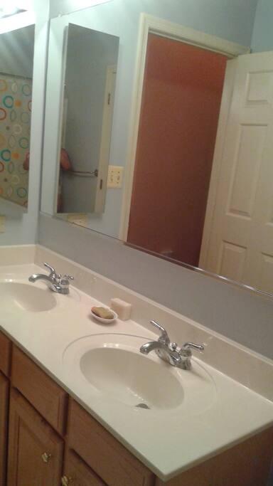 Double sink in bathroom next to bedroom