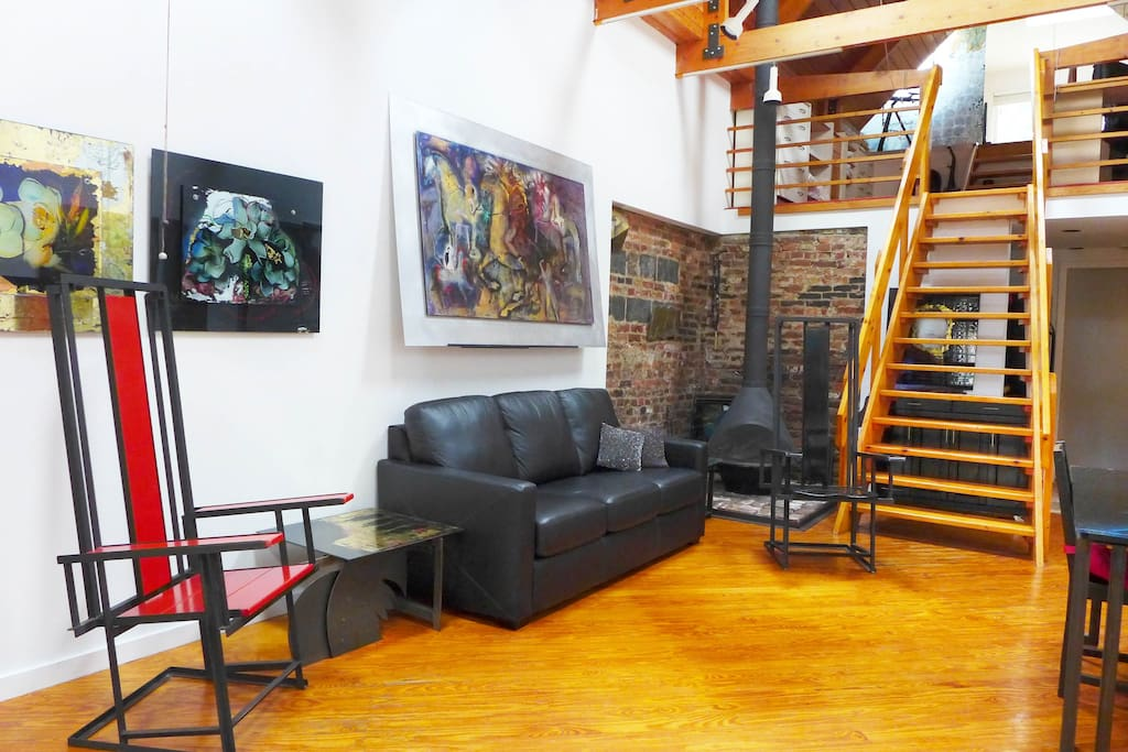 View of the lovely artwork, fireplace, and sleeper sofa