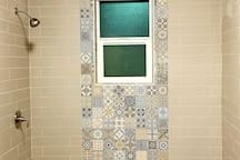 Large bright shower with fun tile work and a spa pebble floor.