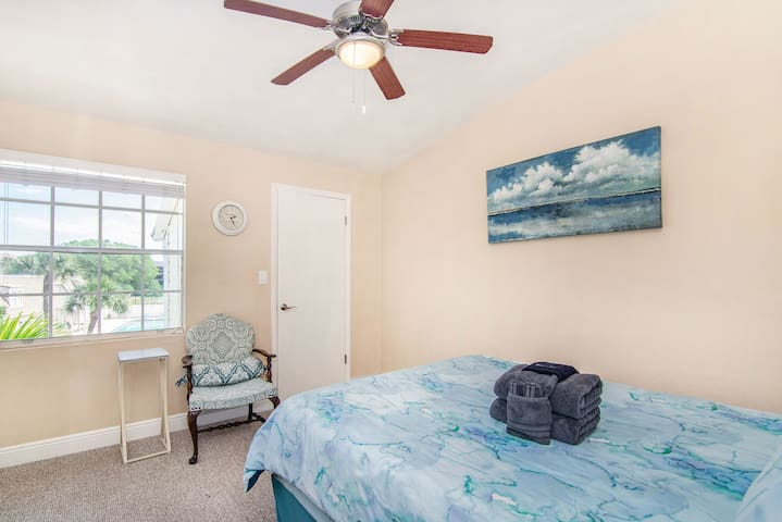 Walk in closet with a smaller chest of drawers, pool towels, luggage rack and laundry hamper