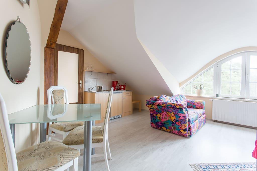 Ferienapartment mit ausklappbarer Couch, offener Küchenzeile und einem Esstisch