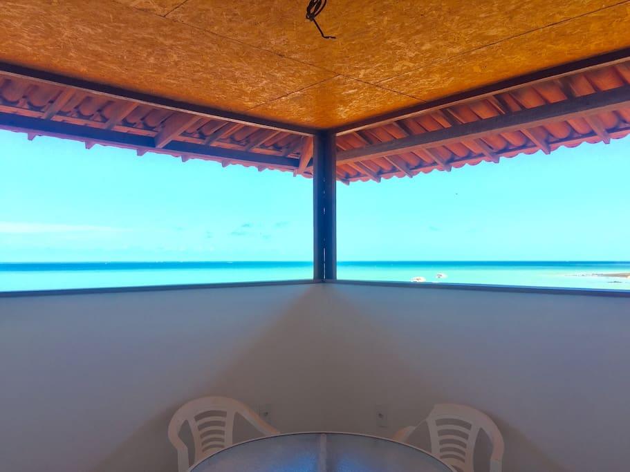Varanda com vista panorâmica da praia, rede e mesa de centro
