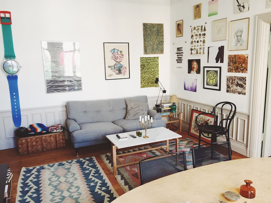Living room with high ceilings, classic furniture, kelim rugs and loads of beautiful prints, papers and art on the walls