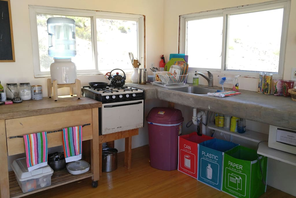 Small kitchen has propane oven & range, microwave,  mini-fridge, and cold running water.