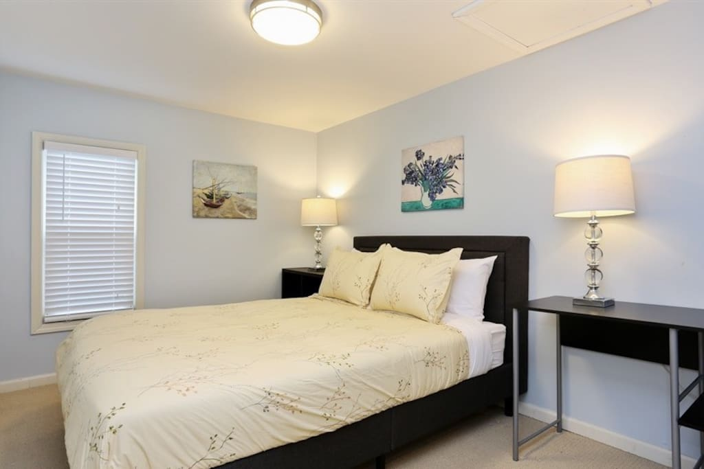 The first bedroom has a quality queen size bed with comfortable linens and a small desk.