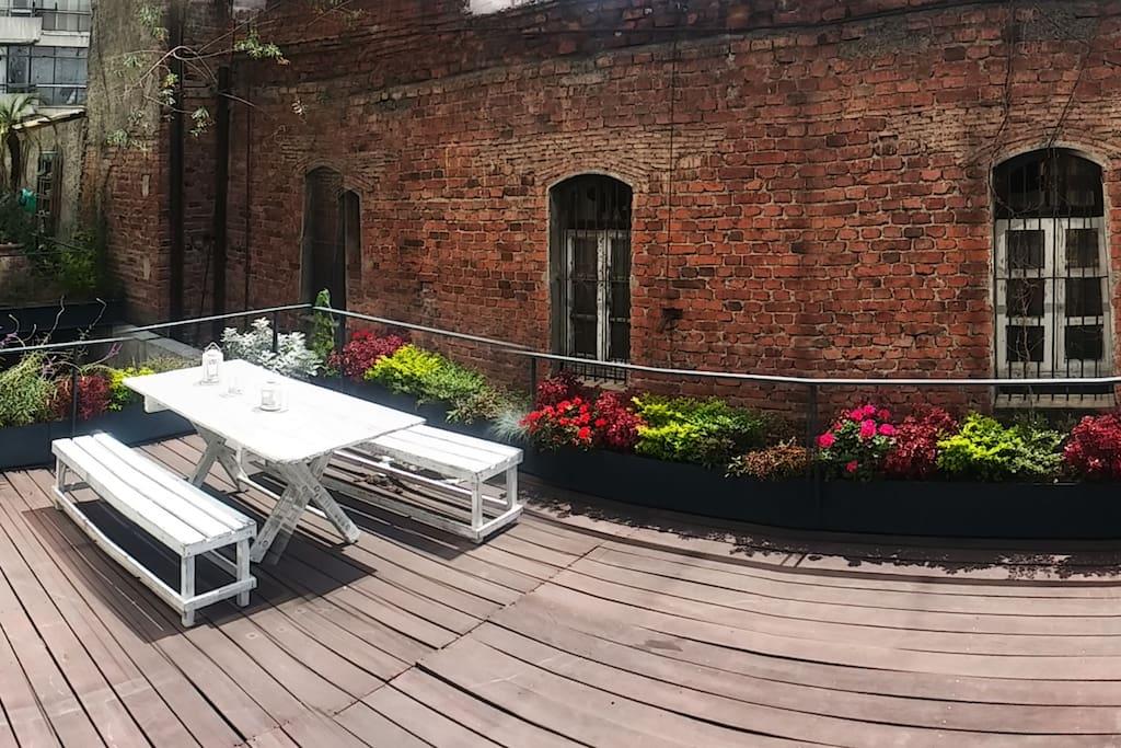 Terraza privada con jardín y mesa. Edificio anexo deshabitado