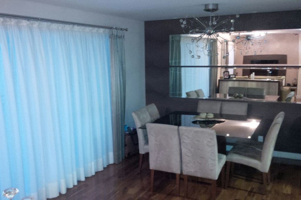 Sala de jantar com mesa quadrada 1,50 x 1,50 m e oito lugares.