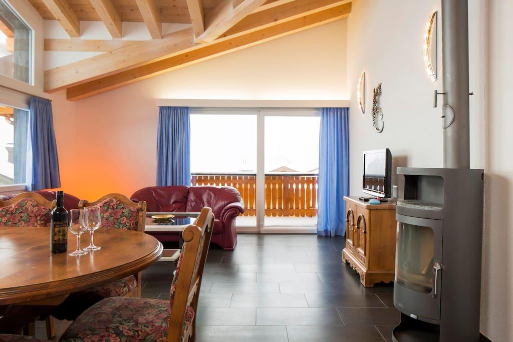 Geräumiger Wohn-Essbereich mit grossem Esstisch, Sofa, Flachbild TV und Holzofen