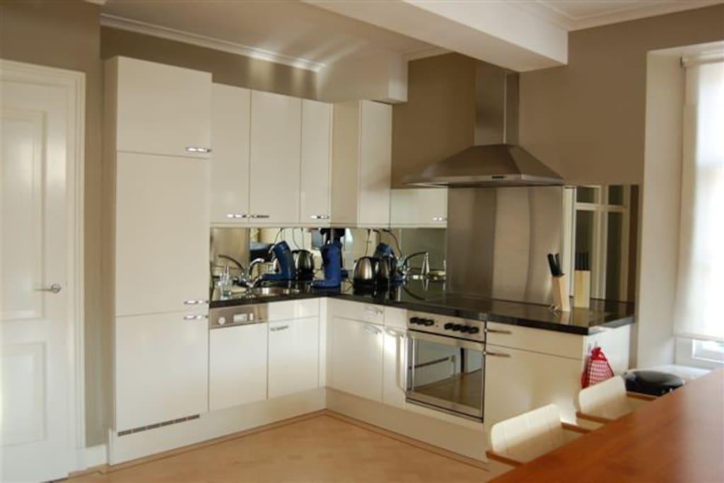 Keuken met vaatwasser, oven, afzuigkap, koelkast met vriesvak..