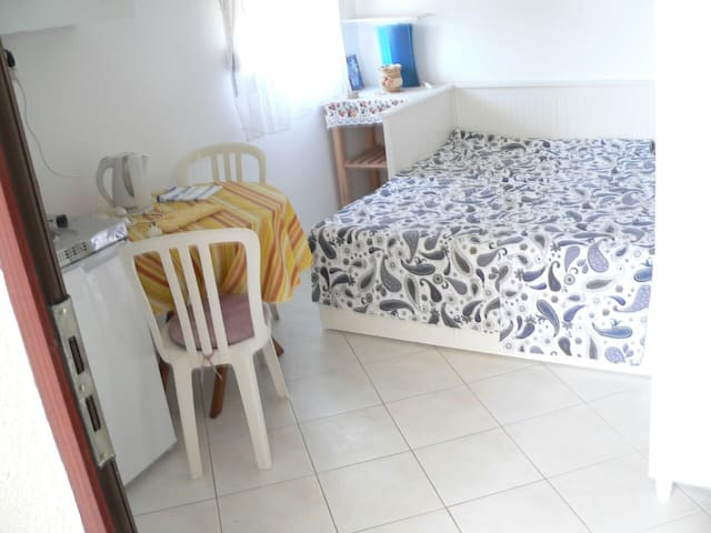 A Room with a bed with matracess which can be extended for two persons.  And small kitchen on the right.