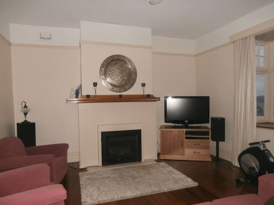 the lounge has lovely floor boards and picture rails as do other rooms - the heater is gas. have recently changed the couch (photo below)