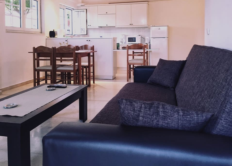 The cosy Living room with doors opening out onto the large patio. There is comfortable sofa, TV, wifi, air conditioning