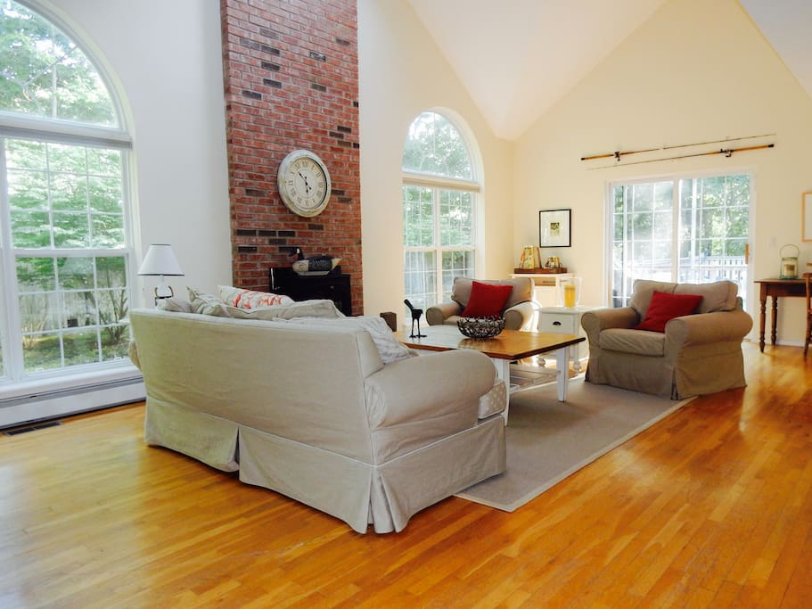 Lovely large open  living room with cathedral ceilings, arched windows slider leading to the deck and pool.