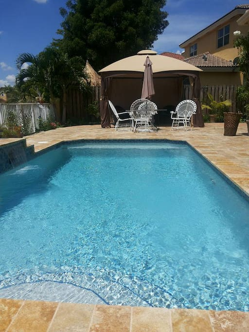 Pool area with gazibo and  round table.