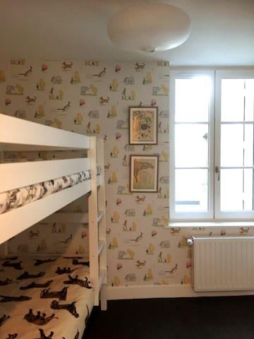 2ème chambre à coucher : lit superposé, étagères avec livres pour enfant et panier à jouets