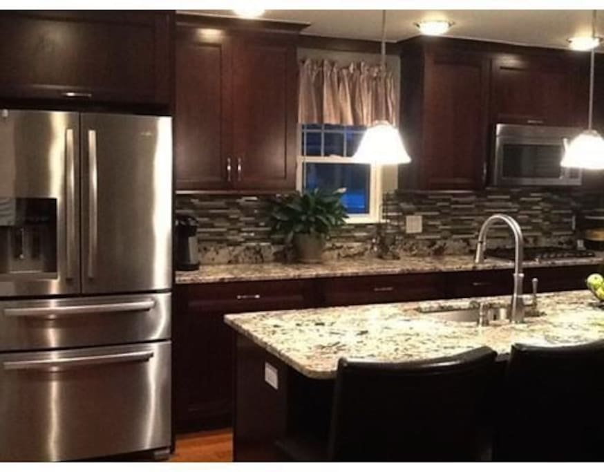 Gourmet kitchen with stainless steel round. Access to refrigerator, dishwasher, microwave, stove and double oven.