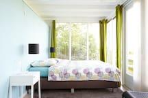 De slaapkamer beneden in de serre met 2-persoons bed en prachtig uitzicht over de weilanden