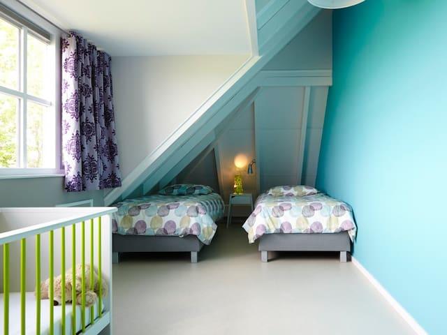 Slaapkamer 4 met twee 1-persoons bedden en een kinderbedje