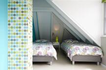 Slaapkamer 5 met twee 1-persoons bedden en een kinderbedje