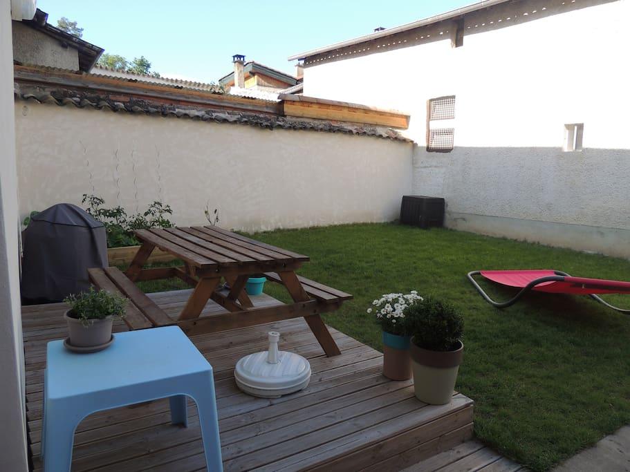 Petit jardin avec barbecue et transats