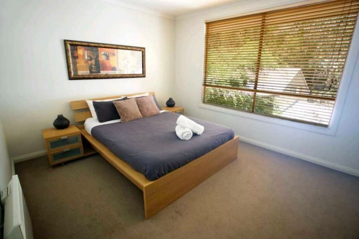 Master bedroom with Queen sise bed, walk in wardrobe, ensuite and T.V. Wall-mounted panel heater to keep you warm