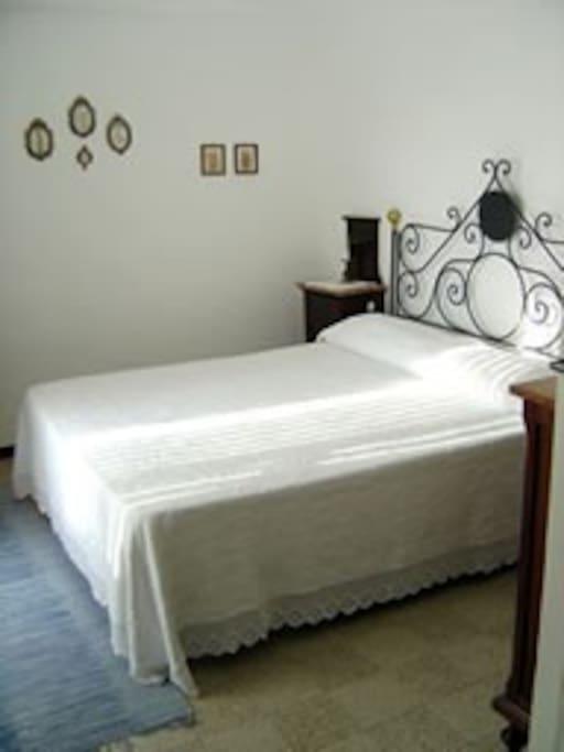 Stanza da letto con l'antica testata in ferro battuto.