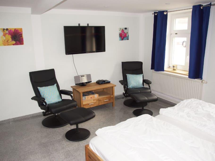 1. Schlafzimmer mit Doppelbett, TV und 2 Relax-Sesseln
